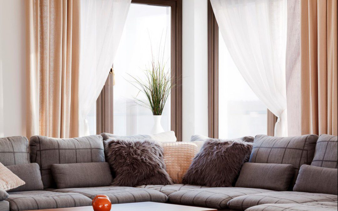sofa with pillows and a sliding glass door on the back