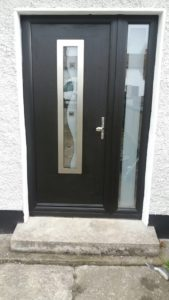 black door with small glass window in front and single glass on the right side